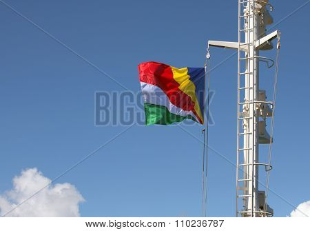 Closeup Of Seychelles Flag Streaming In The Wind On The Mast Of The Ship Against Bright Blue Sky