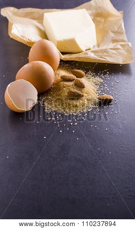 Products for baking. Baking ingredients eggs, brown sugar, almonds, butter on baking paper.