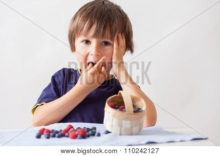 Child, Sitting Behind A Table With Raspberries And Blueberries