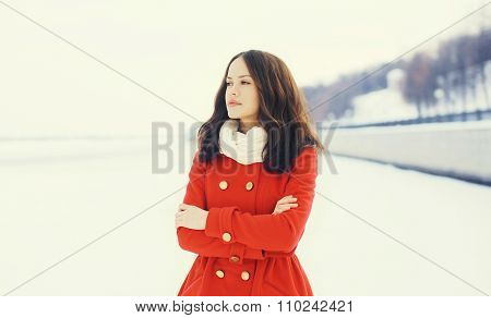 Beautiful Woman Wearing A Red Coat And Scarf Over Snow In Winter Day