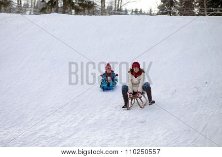 Boy And Mom, Sitting On A Sledge, Going Down On The Hill
