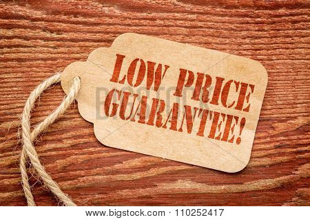 low price guarantee - sign on paper price tag against a rustic barn wood