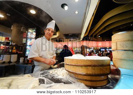 SINGAPORE - NOVEMBER 08, 2015: cook prepare food on the food court of The Shoppes at Marina Bay Sands. The Shoppes at Marina Bay Sands is one of Singapore's largest luxury shopping malls