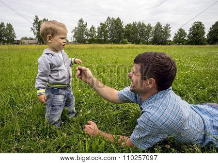 Father Lying On His Stomach Tickles Son 1.3 Years With  Sprig .