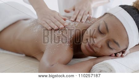 Female getting a salt scrub beauty treatment in the health spa