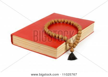 Book With A Red Cover And Wooden Rosary.