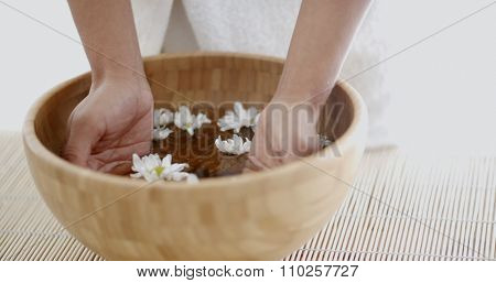 Close up of a female hands with bowl of aroma spa water on table