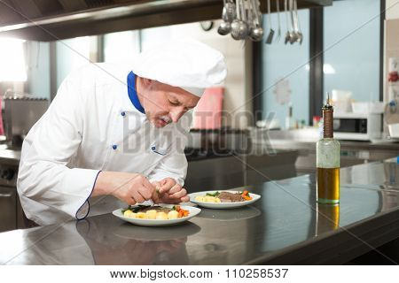 Male chef dressed in white uniform decorating a dish
