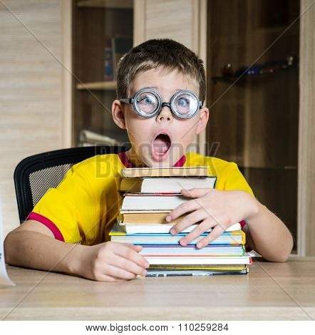 Confused funny schoolboy screaming near the huge stack of books. Education.