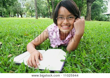 Young girl reading in the park.