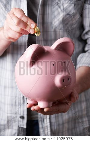 Man Putting Coin Into Large Piggy Bank