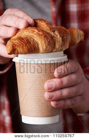 Man Holding Takeaway Coffee And Croissant
