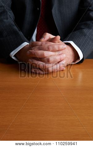 Businessman Sitting At Desk With Folded Hands