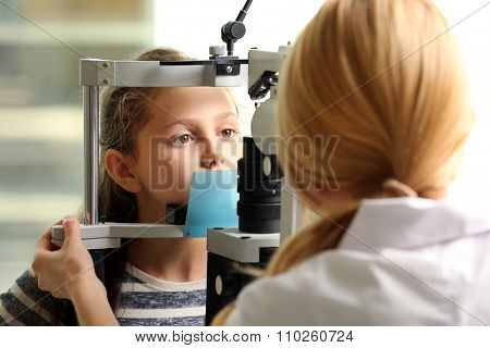 Adult female doctor examing small girl patient