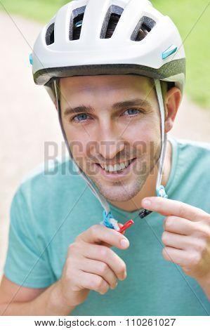 Man Fastening Strap Of Cycle Helmet