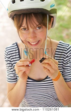 Young Woman Fastening Strap Of Cycle Helmet
