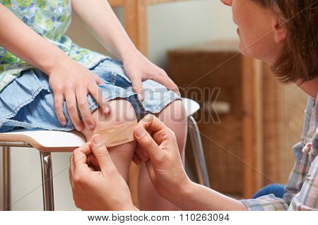 Mother Applying Adhesive Bandage To Daughter's Knee