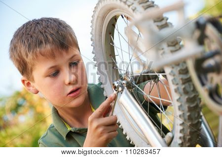 Boy Fixing Wheel Of Bike