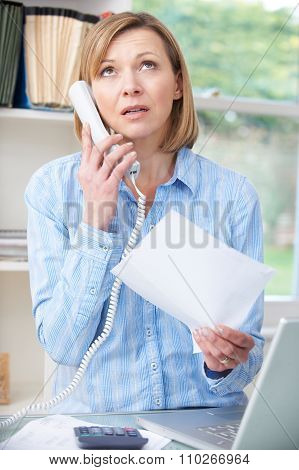 Frustrated Woman On Telephone In Home Office
