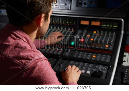 Engineer Working At Mixing Desk In Recording Studio