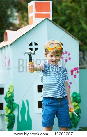 Young Boy Pretending To Be Workman Outside Palyhouse