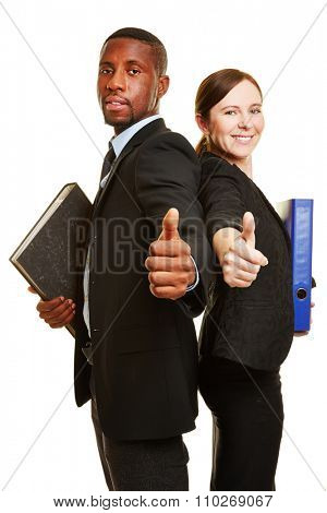 Two successful business people with files holding their thumbs up