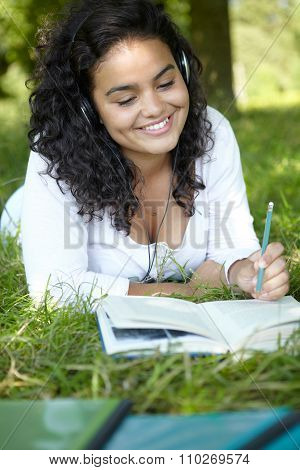 Carefree Student Revising And Listening To Music In Park