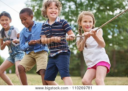 Group of kids pulling a rope at the park
