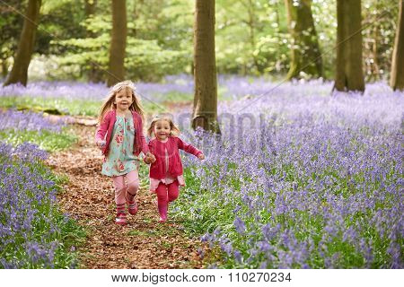 Two Girls Running Through Bluebell Woods Together