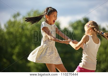 Two happy girls dancing in a circle having fun in summer