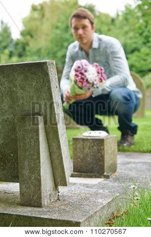 Man Laying Flowers On Grave