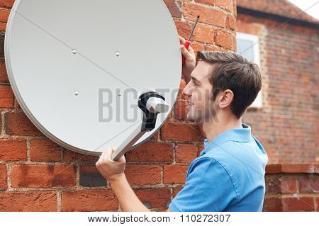 Man Fitting Tv Satellite Dish To House Wall