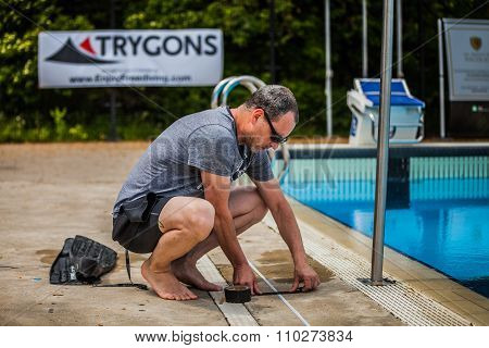 Staff Member Placing The Tape On The Side Of The Pool For Measurement.
