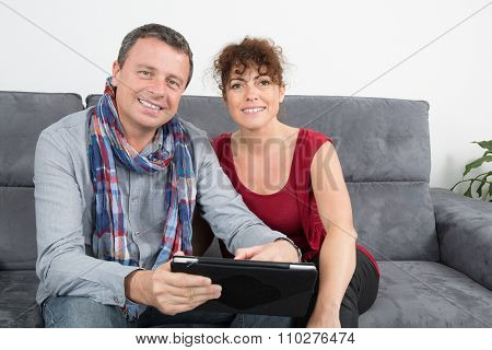 Middle-aged Couple Websurfing On Internet With Tablet