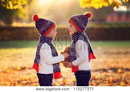 Adorable Little Brothers With Teddy Bear In Park On Autumn Day