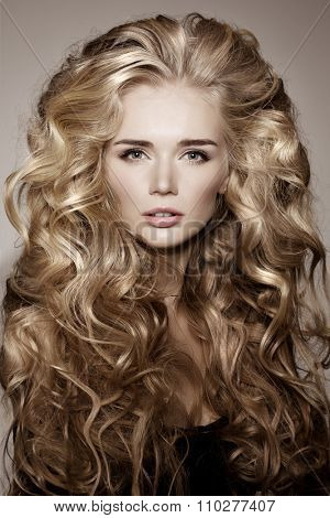 Model with blonde long hair. Waves Curls Hairstyle. Hair Salon. Updo. Fashion model with shiny hair. Woman with healthy hair girl with luxurious haircut. Hair loss Girl with hair volume.