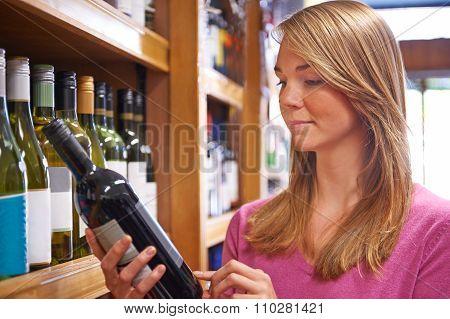 Woman Choosing Bottle Of Red Wine In Supermarket