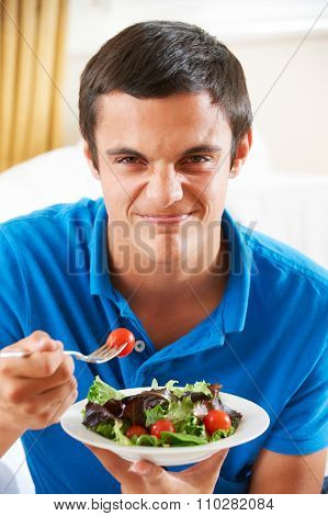 Teenage Boy Pulling Face Whilst Eating Healthy Salad