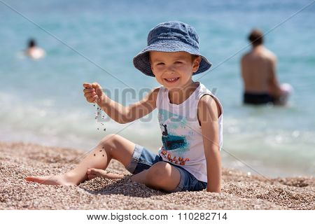 Cute Boy, Playing With Pebbles On The Beach