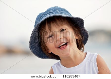 Adorable Portrait Of A Happy Boy, Smiling At The Camera