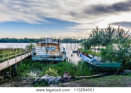 Two Moored Boats Near A Pontoon, In Summer Season. Horizontal View Of A Pontoon, A Rusty Boat Floati