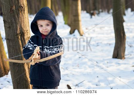 Little Boy, Playing With Crossbow In The Park