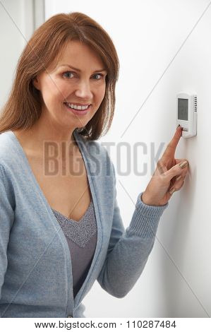 Smiling Woman Adjusting Thermostat On Home Heating System