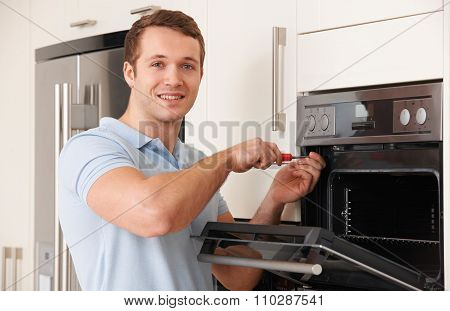 Engineer Reapiring Domestic Oven In Kitchen