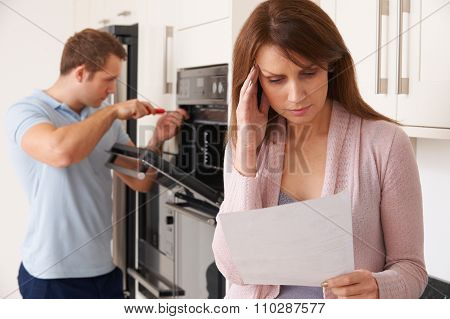 Woman Looking Worried At Cost Of Repair Bill For Domestic Applia