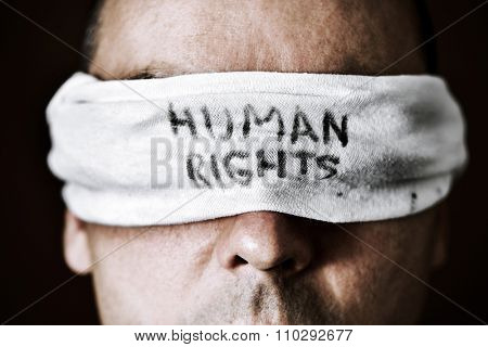 closeup of a young man with a blindfold in his eyes with the text human rights written in it, as a symbol of oppression or repression, with a dramatic effect