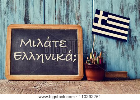 a chalkboard with the question question do you speak greek? written in greek, a pot with pencils, an eraser and the flag of Greece, on a wooden desk