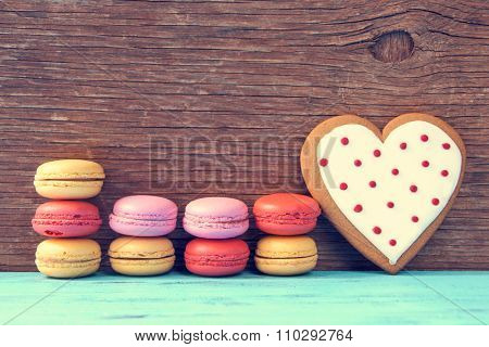 some appetizing macarons with different colors and flavors and a homemade heart-shaped cookie on a blue wooden surface, against a rustic wooden background