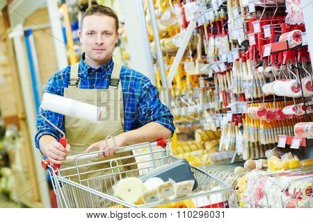 happy hardware store worker or painter buyer customer with shopping cart looking at the camera