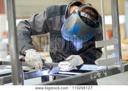 Man leaning over welding